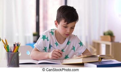boy writing to notebook at home - education, childhood and...