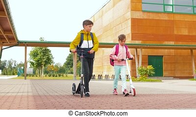 happy school children with backpacks and scooters - ...