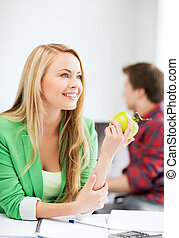 student girl with green apple in college