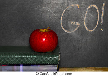 Education Concept With Apple On Stack Of Books Blackboard Background