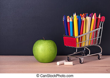 education concept with green apple, chrome shopping cart, pens, crayons, chalks on black chalkboard background, close up