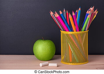 Education Concept With Green Apple Pencils Chalks Over Black Chalkboard Background Close Up