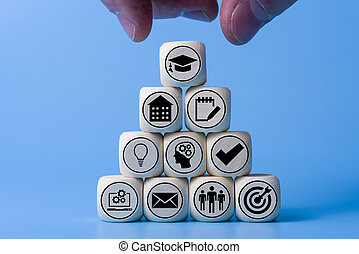Education concept with icons on wooden cubes, blue background.