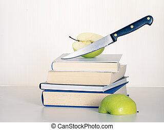 Education cuts concept. Teacher's apple sliced in half.