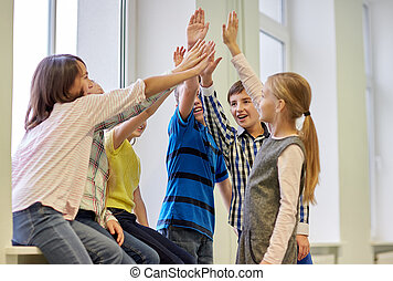 group of smiling school kids making high five - education,...