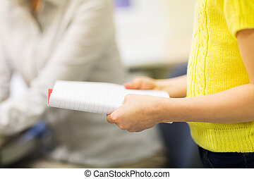 close up of girl with notebook at school lesson