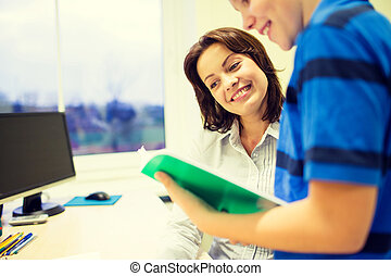 school boy with notebook and teacher in classroom