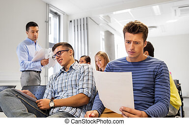 students with tests and teacher at lecture hall