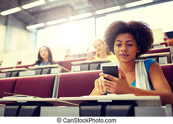 african student girl with smartphone at lecture