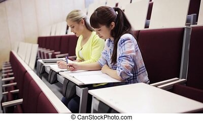 student girls with notebooks in lecture hall - education,...