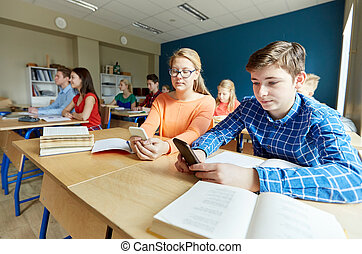 students with smartphone texting at school