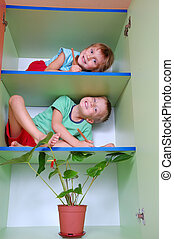 two smiling kids with pencils on shelves playing school