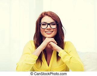 smiling teenage girl in eyeglasses at home
