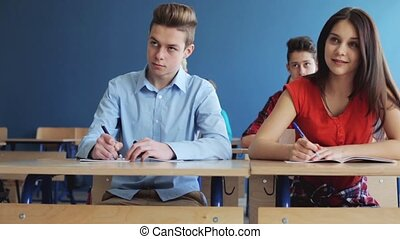 students with notebooks writing test at school - education,...
