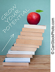 Personal development and progress in education concept with large pile of books and arrow pointing upwards