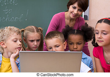 Portrait of pupils looking the laptop with teacher near by
