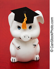 Education Savings - Piggy bank with graduation cap on a wood...