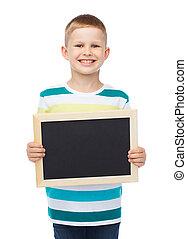 smiling little boy holding blank black chalkboard