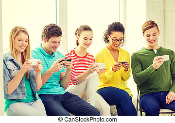 smiling students with smartphone texting at school -...
