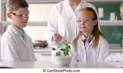 students and teacher with plant at biology class -...