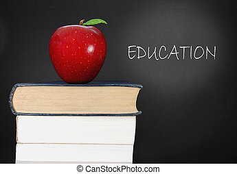 Education - Stack of books and an apple next to a blank ...
