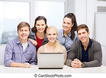 smiling students with laptop at school