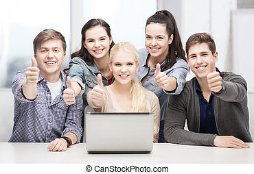 smiling students with laptop showing thumbs up - education,...