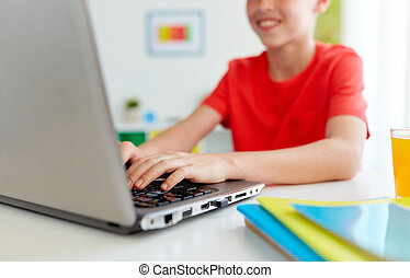 student boy typing on laptop computer at home