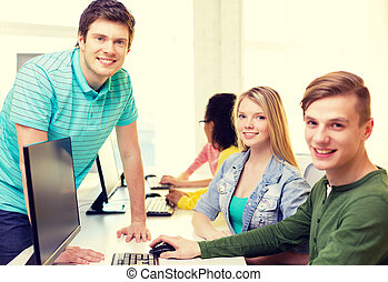 group of smiling students in computer class - education,...