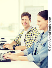 smiling boy with girl in computer class at school