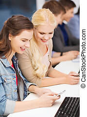 students with computer monitor and smartphones - education,...