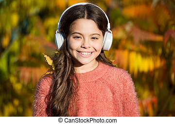 Educational and downloadable audio books for children. Kid girl relaxing near autumn tree with headphones. Music for autumn mood. Listening song. Enjoy music fall day. Autumn walks with nice songs