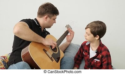 Educational process of playing guitar between dad and his...