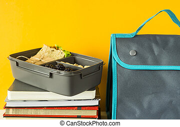 Educational supplies with school lunch on yellow