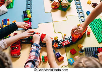 Educational toys for preschool and kindergarten child. Child playing with constructor blocks at class.