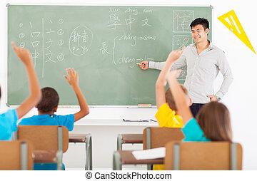 smiling educator teaching Chinese language to group of primary kids
