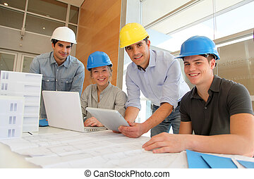 Educator with students in architecture working on electronic...