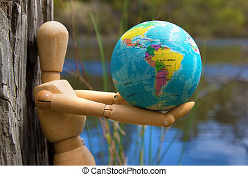 Eearth globe in hands of wooden doll wildlife and environment protection concept