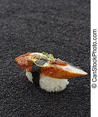 Eel sushi nigiri on black sesame background