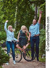 een, aantrekkelijk, gezin, geklede, in, vrijetijdskleding, op een fiets, rijden, hebben vermaak, en, het springen in, een, park.