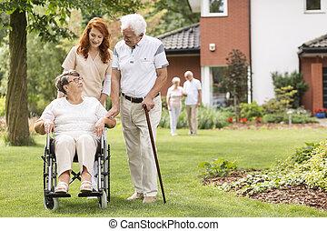 een, bejaarden, invalide, paar, met, hun, huisbewaarder, in de tuin, buiten, van, een, particulier, rehabilitatie, clinic.