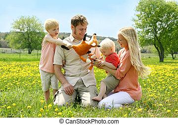 een, gelukkige familie, van, vier mensen, moeder, vader, jong kind, en, toddler, zijn, spelend, met, volgestopt, vos, speelgoed, buiten, in, een, paardenbloem, bloemenweide, op, een, lente, day.
