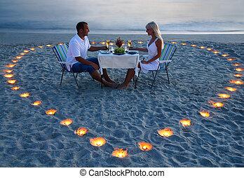 een, jonge, minnaars, paar, aandeel, een, romantisch diner, met, kaarsjes, hart, op, de, zee, zand strand