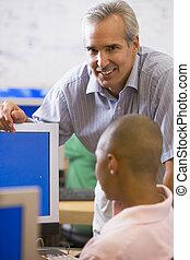 een, leraar, besprekingen, om te, een, schooljongen, gebruik, een, computer, in, een, secundair onderwijs