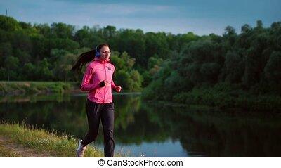 een, meisje, in, een, roze, jas, en, zwart gehijg, looppas, dichtbij, de, rivier, in, headphones, het bereiden, voor, de, marathon
