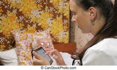 een, vrouwtje arts, interrogates, een, patiënt, op, home., zij, schrijft, een, anamnese, om te, de, tablet, computer.