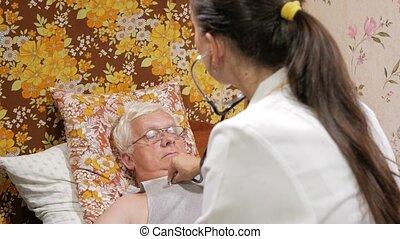 een, vrouwtje arts, luistert, om te, een, patiënt, met, een, phonendoscope, op, home., de, man, is, het liggen, op, de, couch.