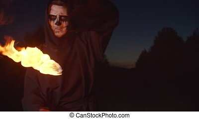 Eerie angel of death in black cloak conjuring, playing with fireball, doing magic stunt of controlling burning sphere, expressing fear and horror while standing in dark nature on halloween at night.