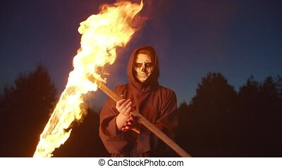 Eerie death reaper in black cloak juggling and frightening with burning scythe at night, showing menace, ruthlessness and horror on halloween while standing over dark forest background.