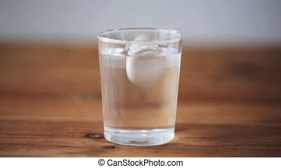 effervescent pill dropping into glass of water
